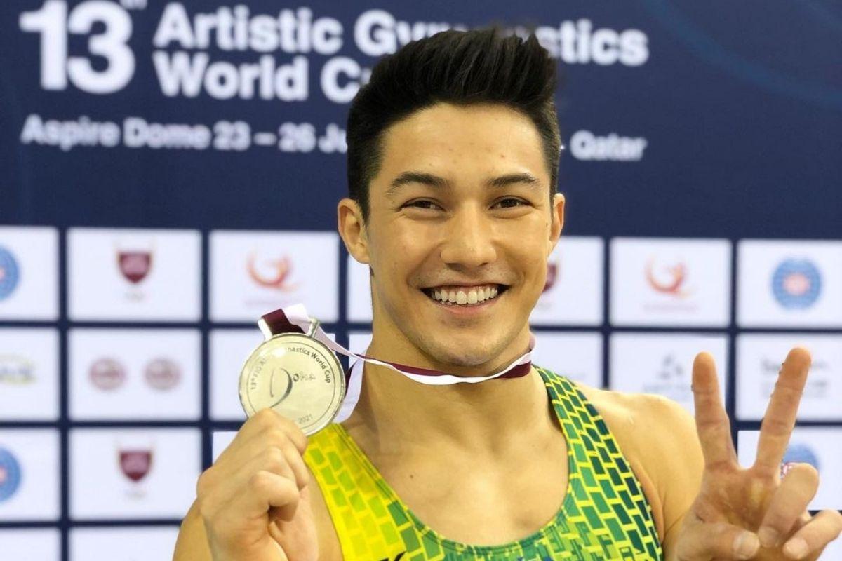 Arthur Nory em retrato sorrindo com uma medalha no pescoço