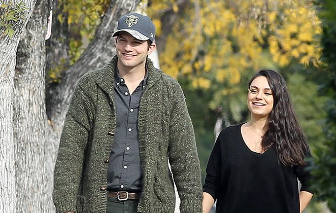 Ashton Kutcher e Mila Kunis caminhando de mãos dadas