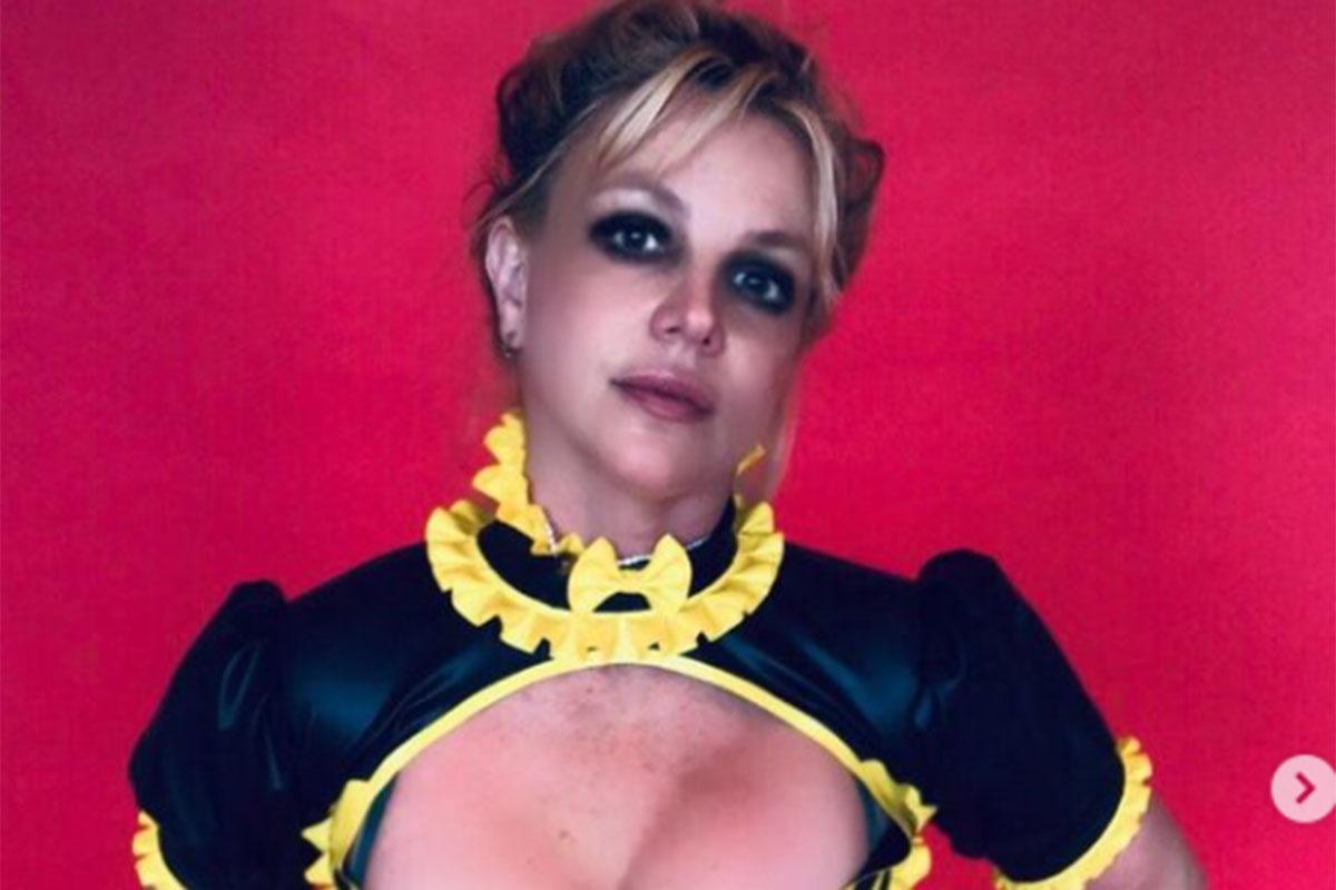 Britney Spears com blusa preta e amarela decotada