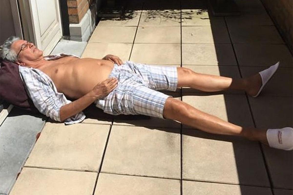 Caetano Veloso deitado, tomando sol na varanda, de camisa aberta
