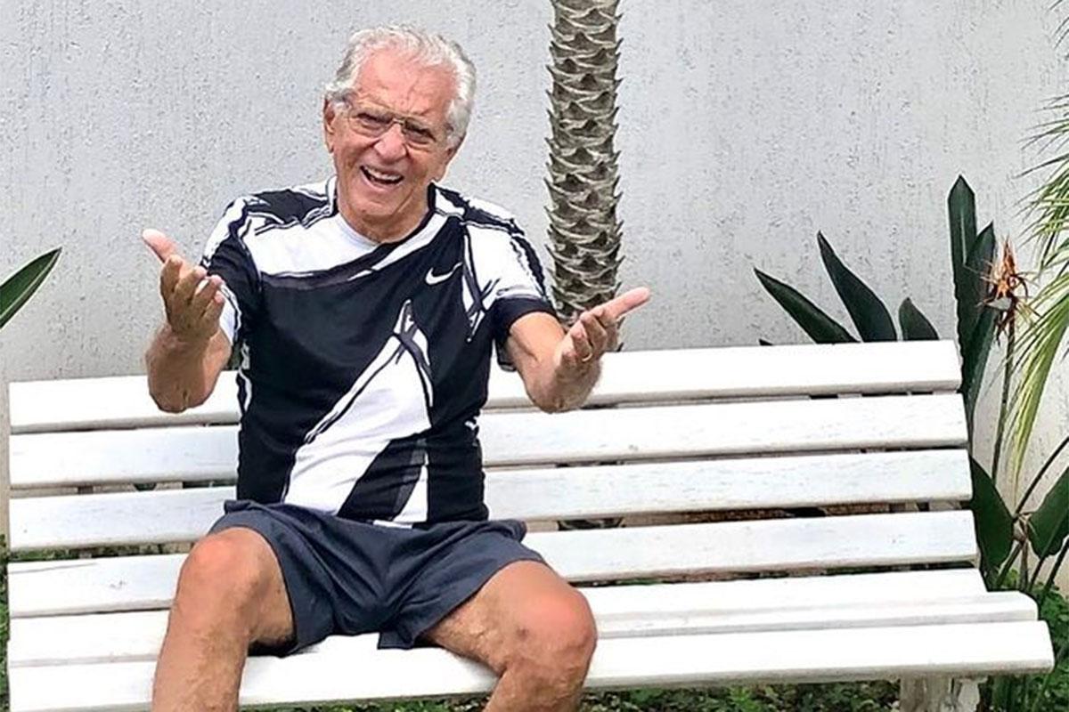 Carlos Alberto de Nóbrega sorridente, de short e camiseta, sentado no banco da Praça