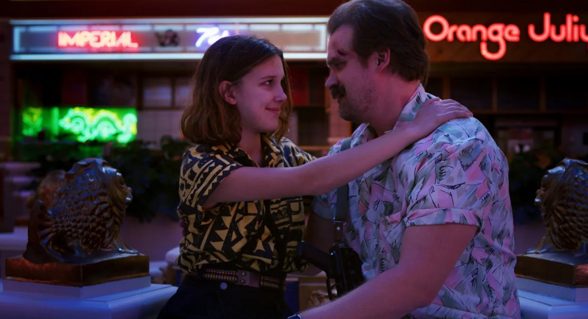 David Harbour Millie Bobby Brown se olham em cena de Stranger Things