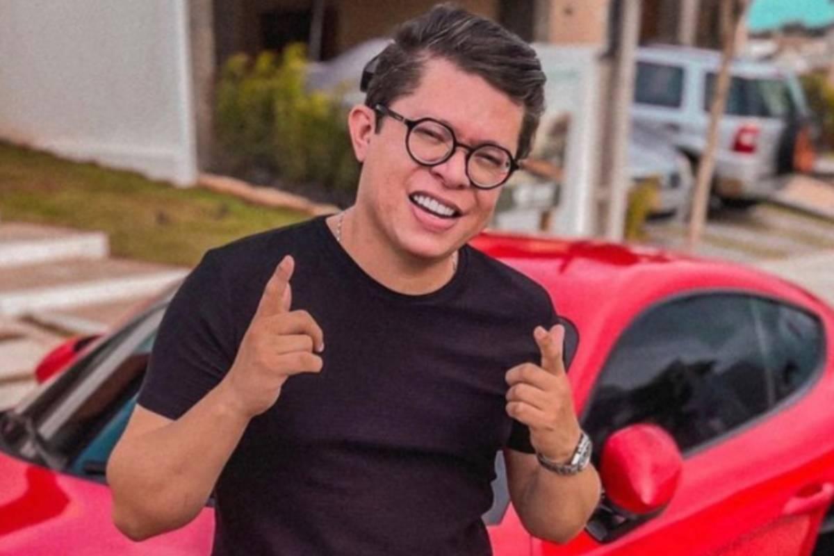 dj ivis na frente de um carro vermelho