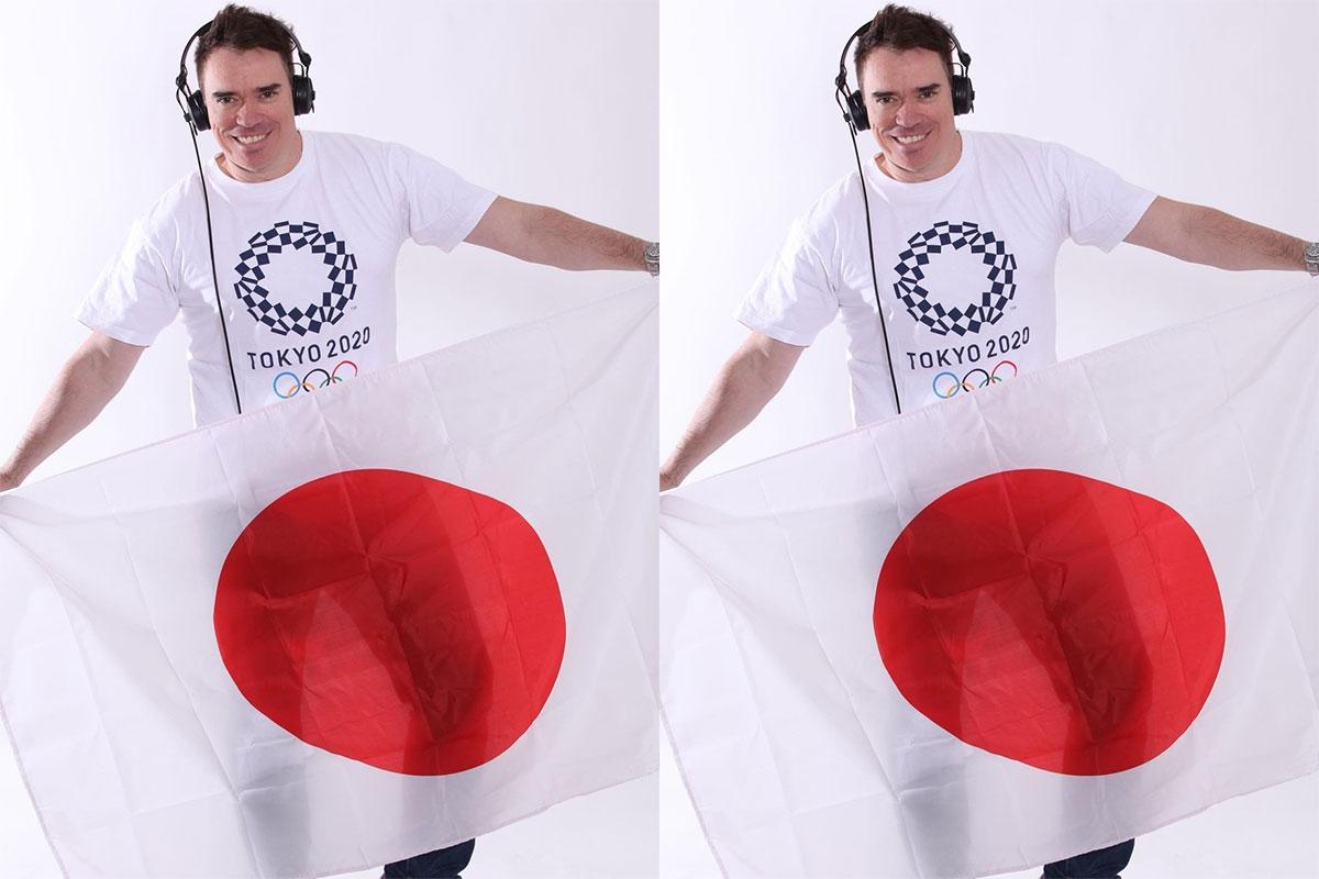DJ Stari, de camiseta com a logomarca da Olimpíada, usa fone e segura a bandeira do Japão