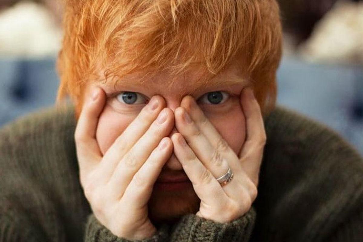 Ed Sheeran com as mãos no rosto, olhando para a câmera