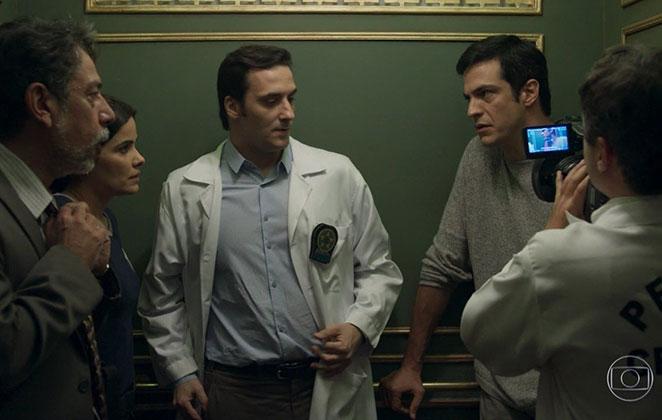 Eric fica preso no elevador com os policiais ao fazer a reconstrução do dia do roubo
