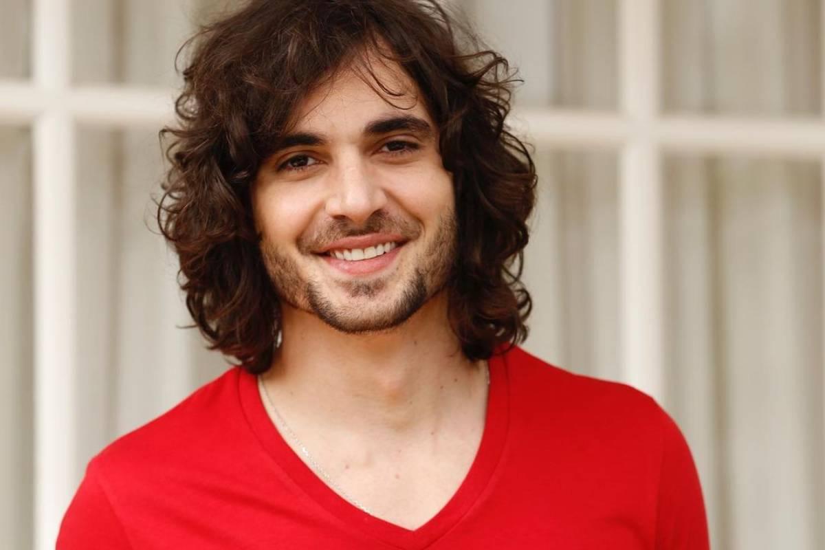 fiuk sorrindo e vestindo uma camiseta vermelha