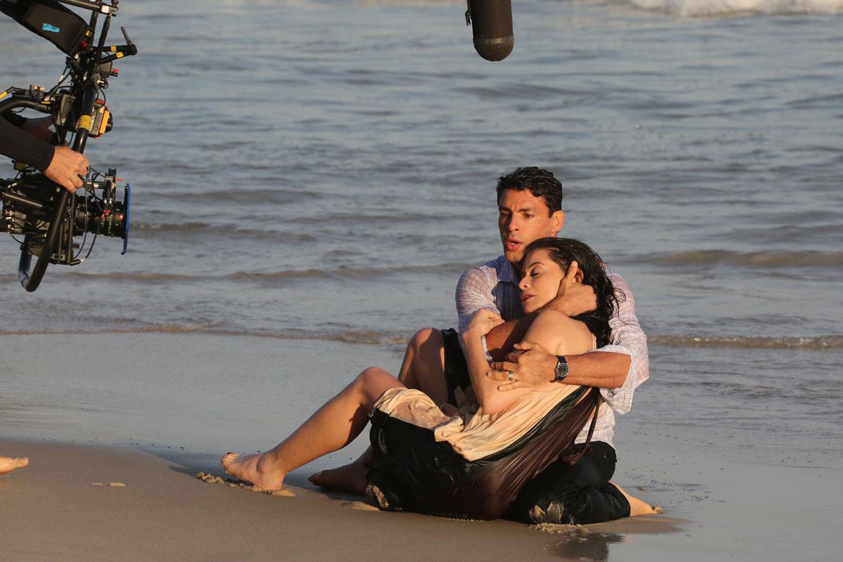 Foto de Cauã Reymond e ALinne Moraes gravando em praia