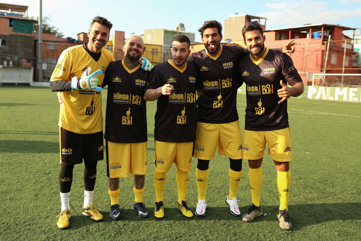 Foto de Gui Napolitano, Bil Araújo e Gui Albuquerque em partida de futebol solidário