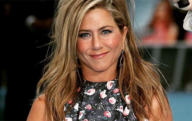 Jennifer Aniston sorridente, de cabelos soltos e roupa florida