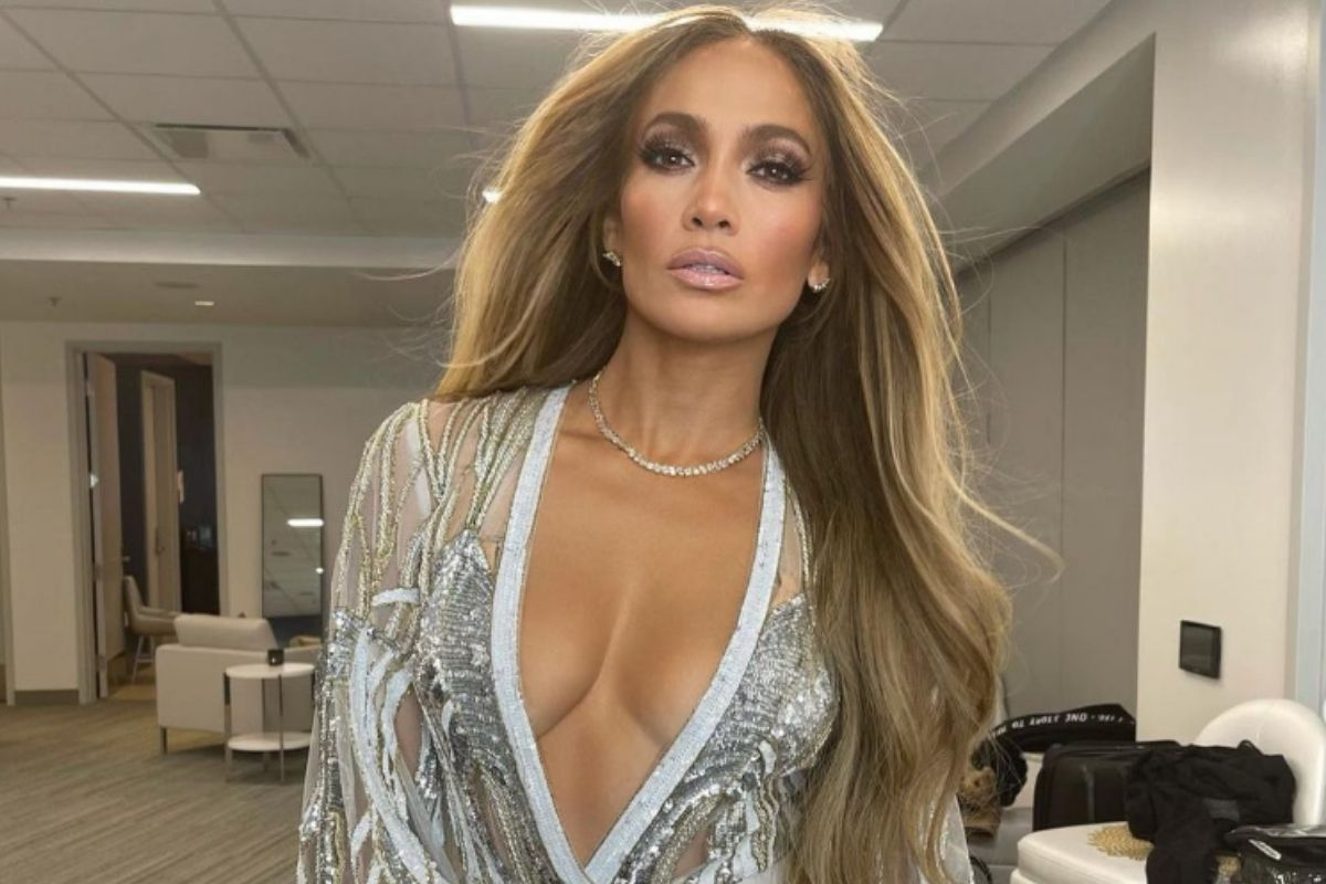 Retrato de Jennifer Lopez maquiada, com roupa branca e cabelos soltos