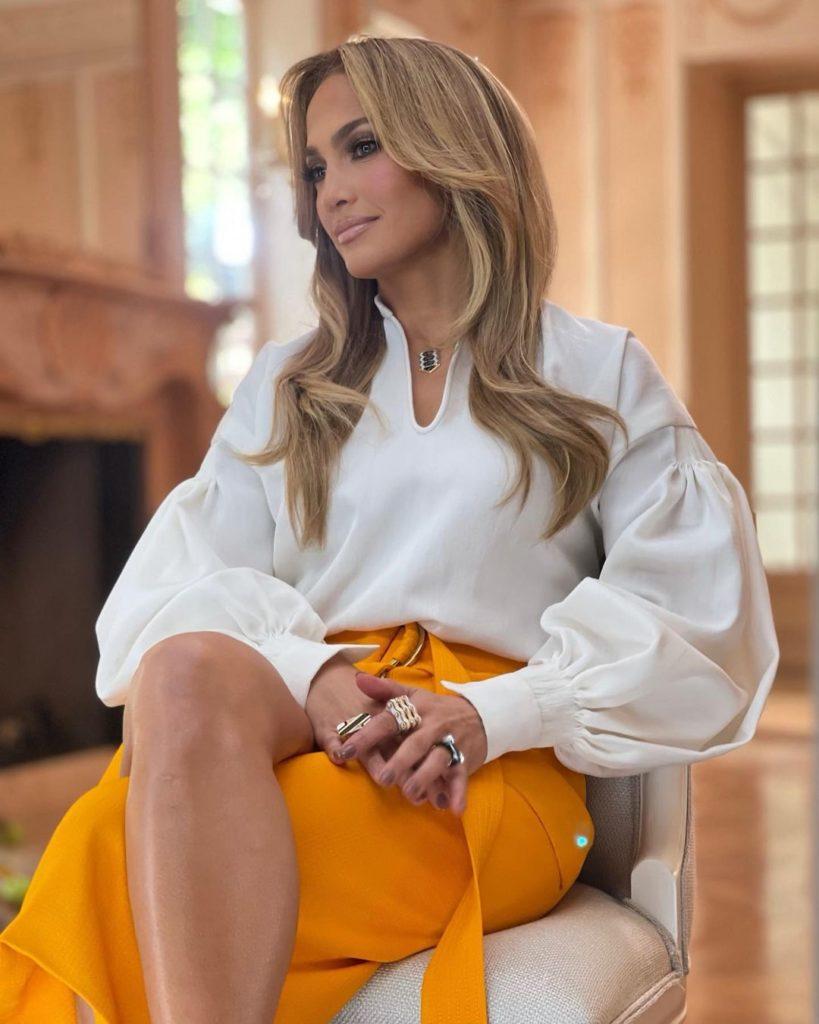 J.Lo de camisa branca e saia laranja