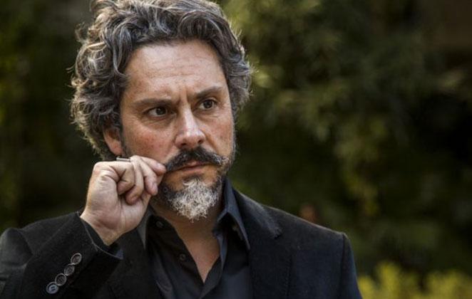 José Alfredo com olhar sério, segurando o bigode