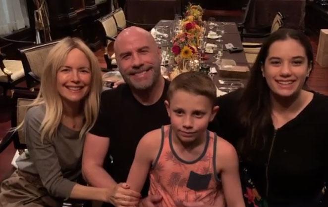 Kelly Preston, com John Travolta e os filhos do casal, sentados à mesa