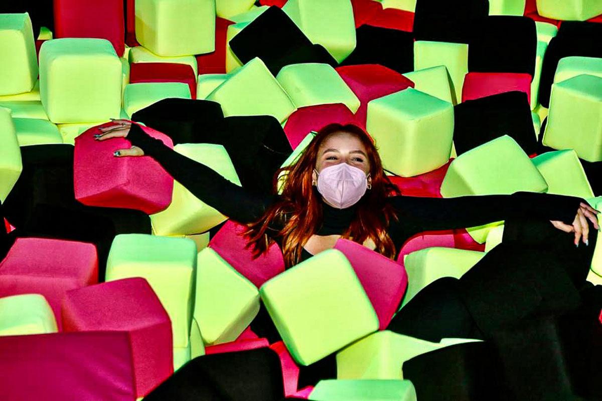 Larissa Manoela de máscara, deitada em blocos coloridos