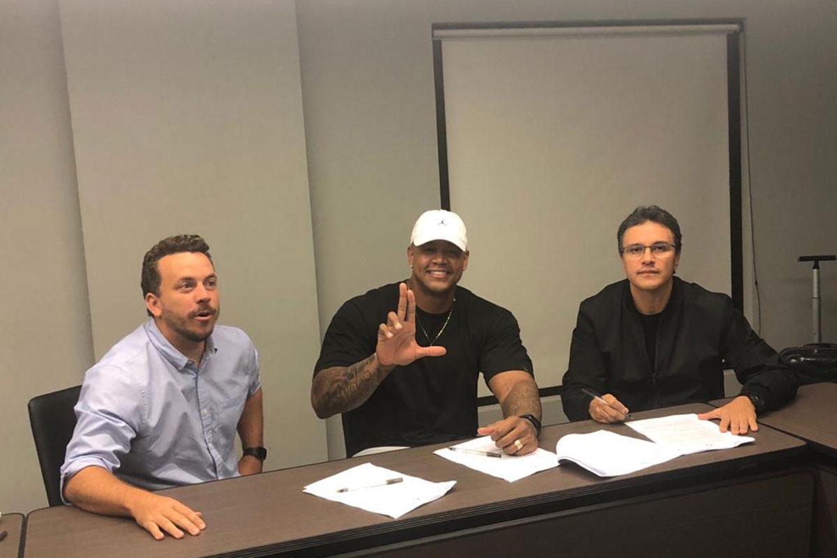 Léo Santana de camiseta preta e boné branco, assinando novo contrato com a Universal Music