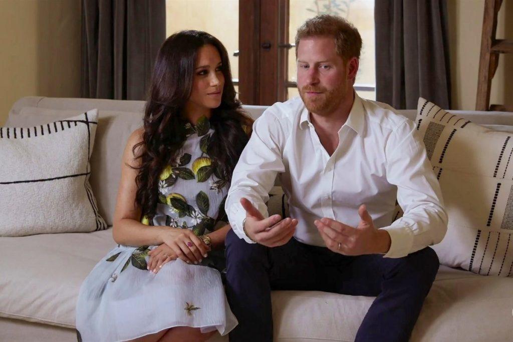 Meghan Markle e Principe Harry sentados no sofa