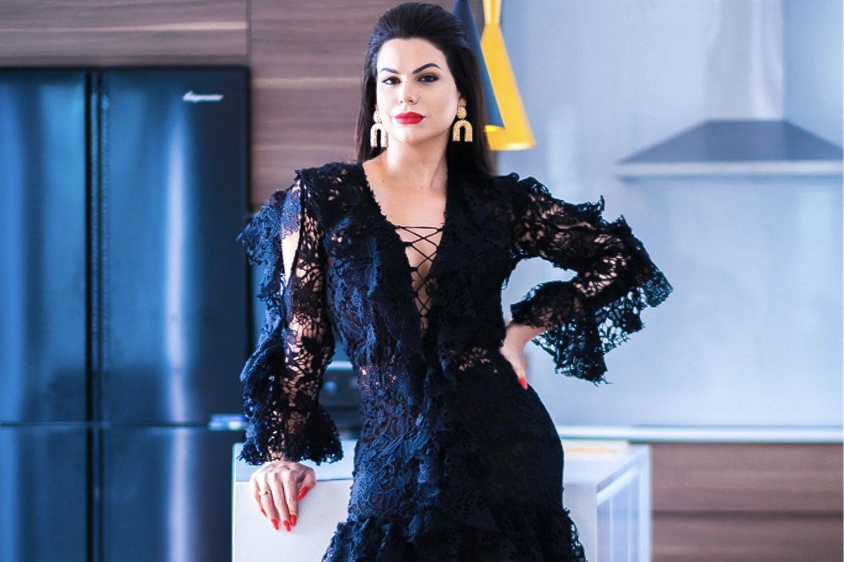 A modelo trans Camila Mantovani elegante, com um vestido preto rendado
