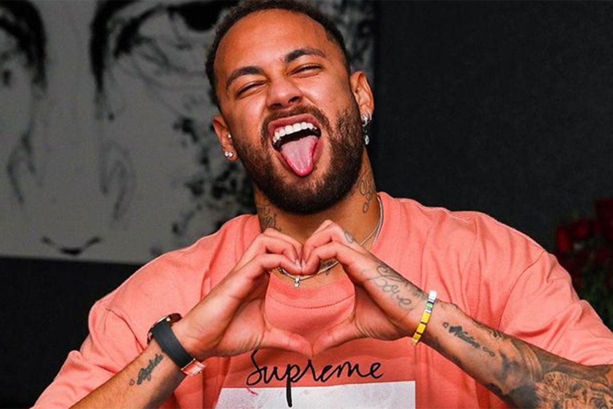 Neymar de camiseta, mostra a língua e faz coração com as mãos