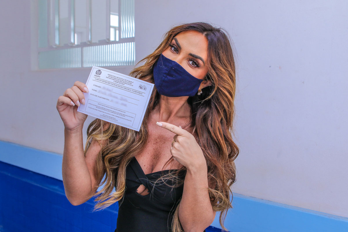 Nicole Bahls em foto segurando carteirinha de vacinação