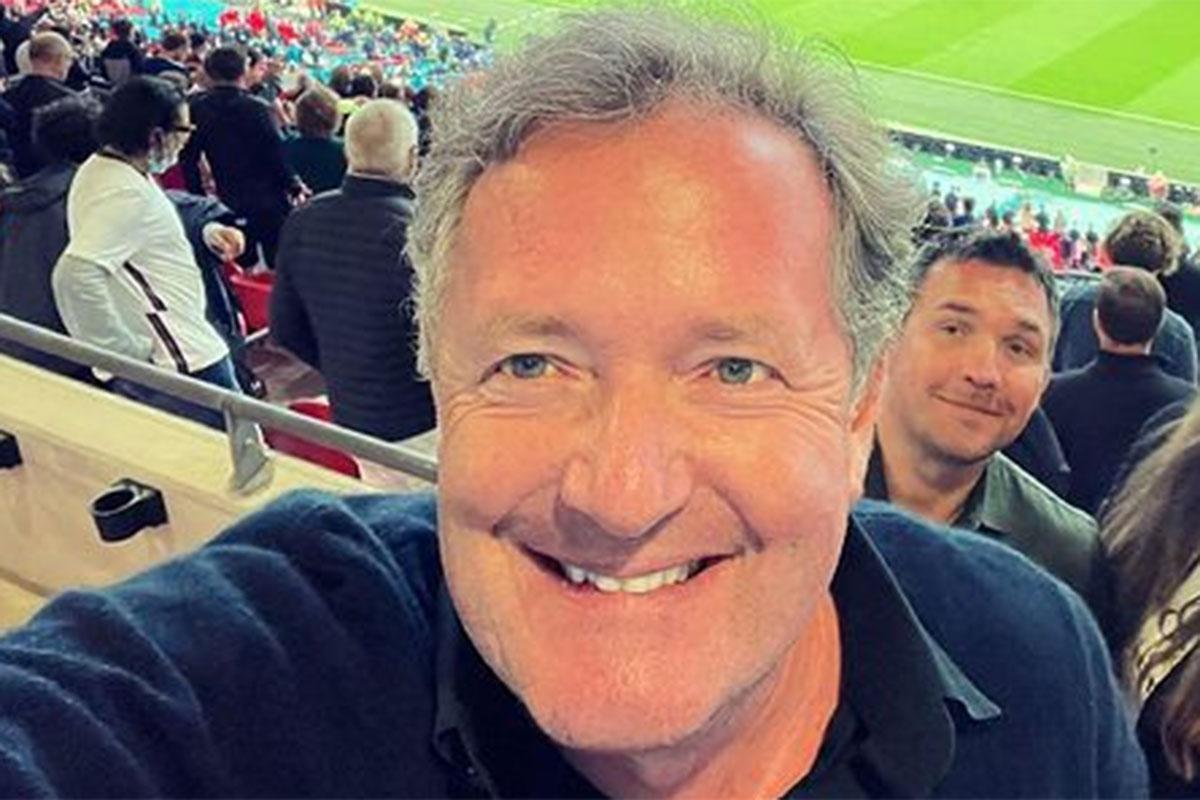 Piers Morgam sorridente, em arquibancada de jogo de futebol