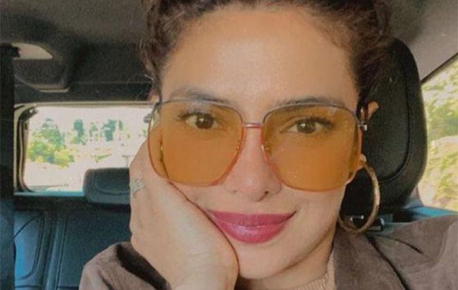 Priyanka Chopra de óculos colorido, com a mão no rosto, dentro do carro