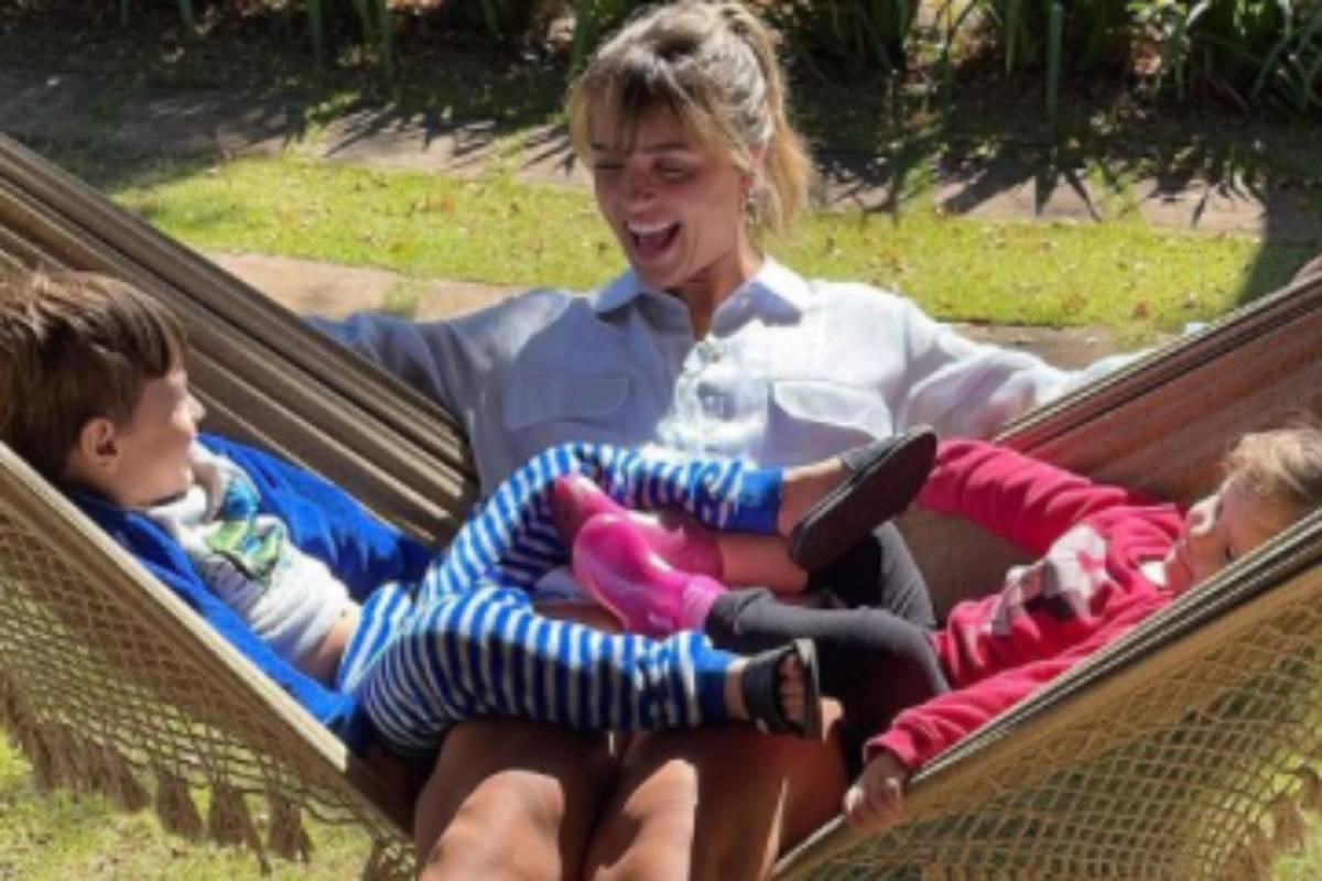 rafa kalimann sentada na rede com crianças da família