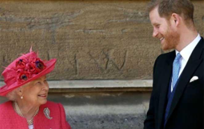 Rainha Elizabeth II de roupa e chapéu vermelho e Príncipe Harry de terno e gravata