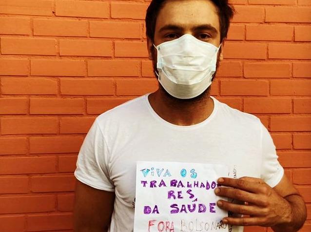 sérgio guizé segurando cartaz enquanto recebe vacina