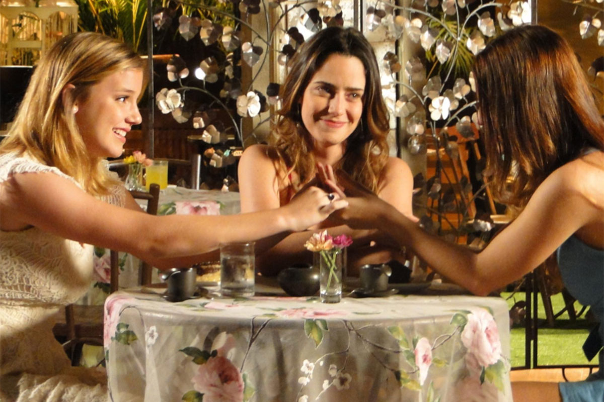 Sofia, Ana e Alice conversando na mesa