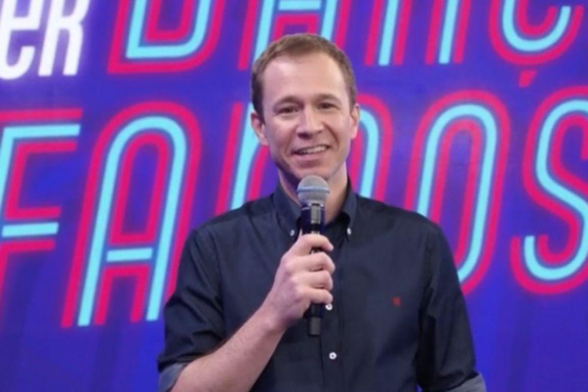 Tiago Leifert sorrindo e segurando microfone