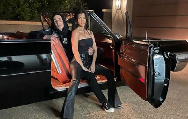 Kourtney Kardashian e Travis Barker abraçados em frente a carrão