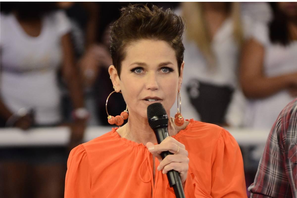 xuxa apresentando o tv xuxa em 2012/2013 com blusa laranja e microfone na mão