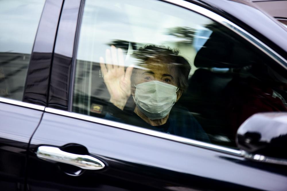 Glória Menezes acenando para os fotógrafos na saída do hospital