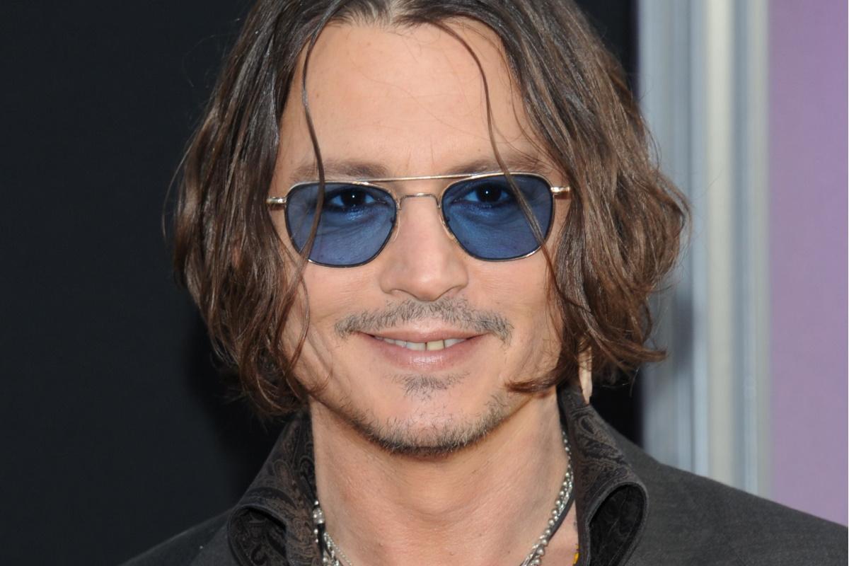 Johnny Depp sorrindo e de oculos