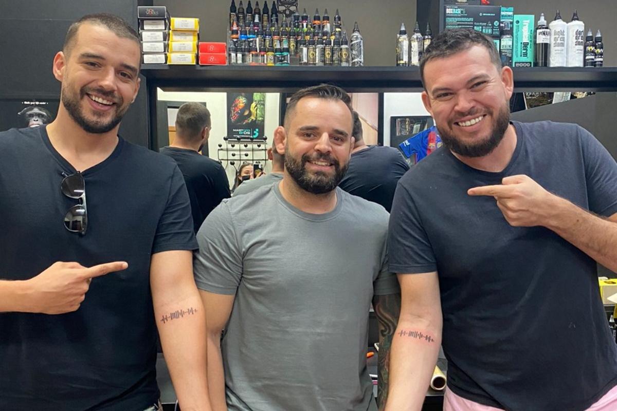 Luiz Henrique e Leo mostrando a tatuagem