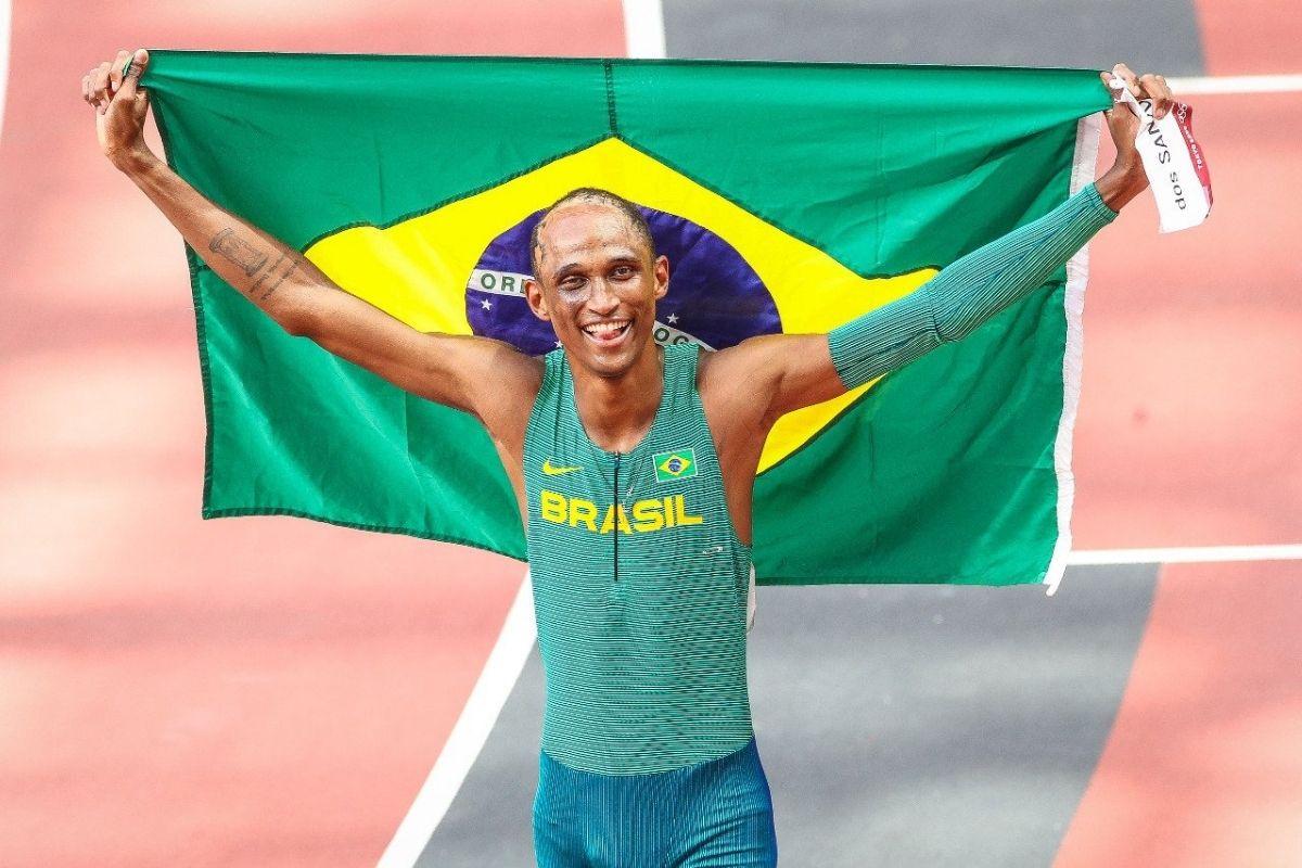 Alison dos Santos com a bandeira do Brasil