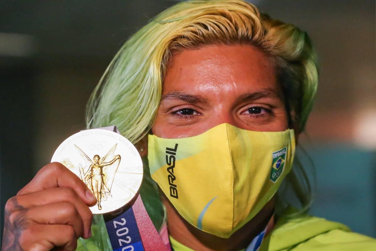 ana marcela com medalha de ouro em aeroporto