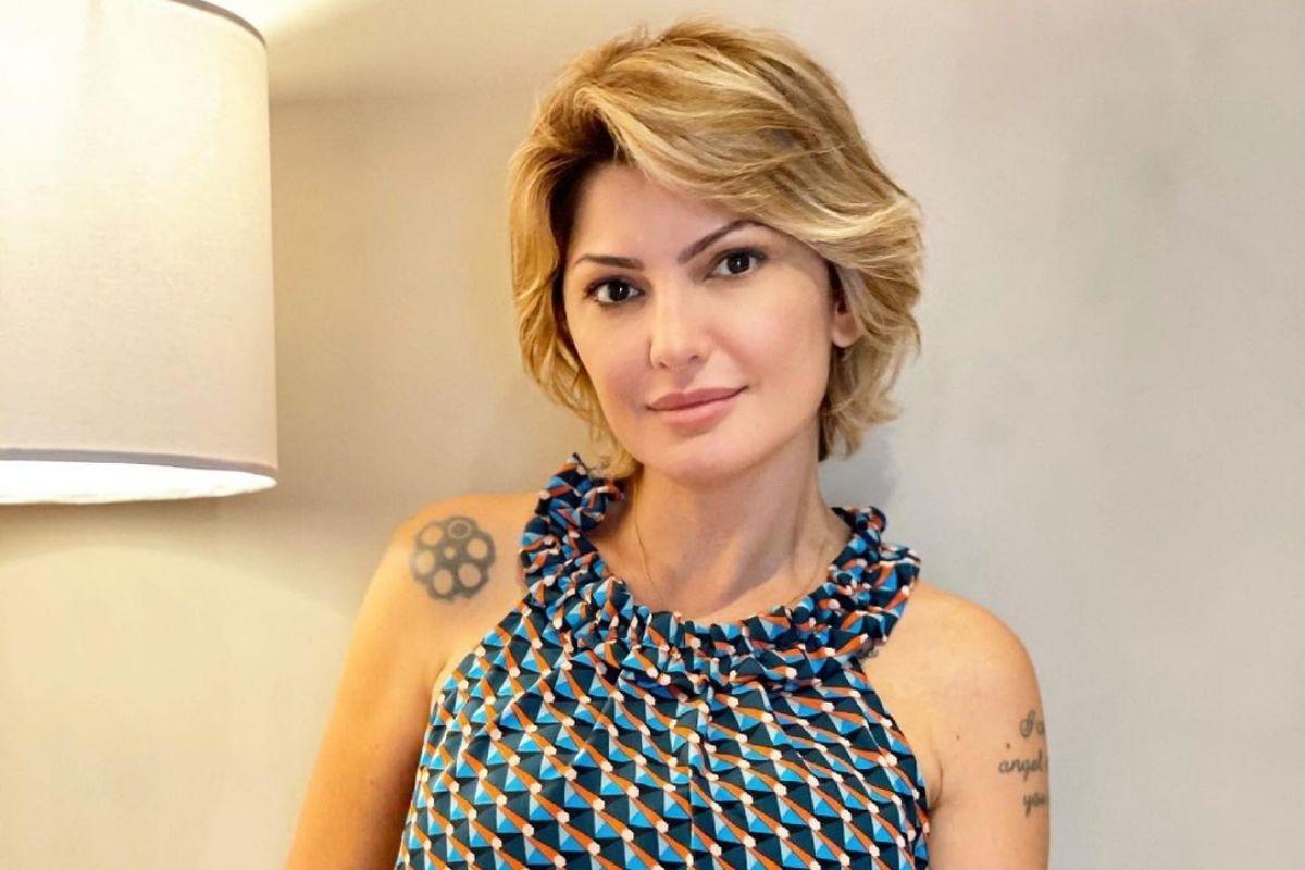 Antônia Fontenelle com cabelo curto, mostrando as tatuagens e usando roupa azul