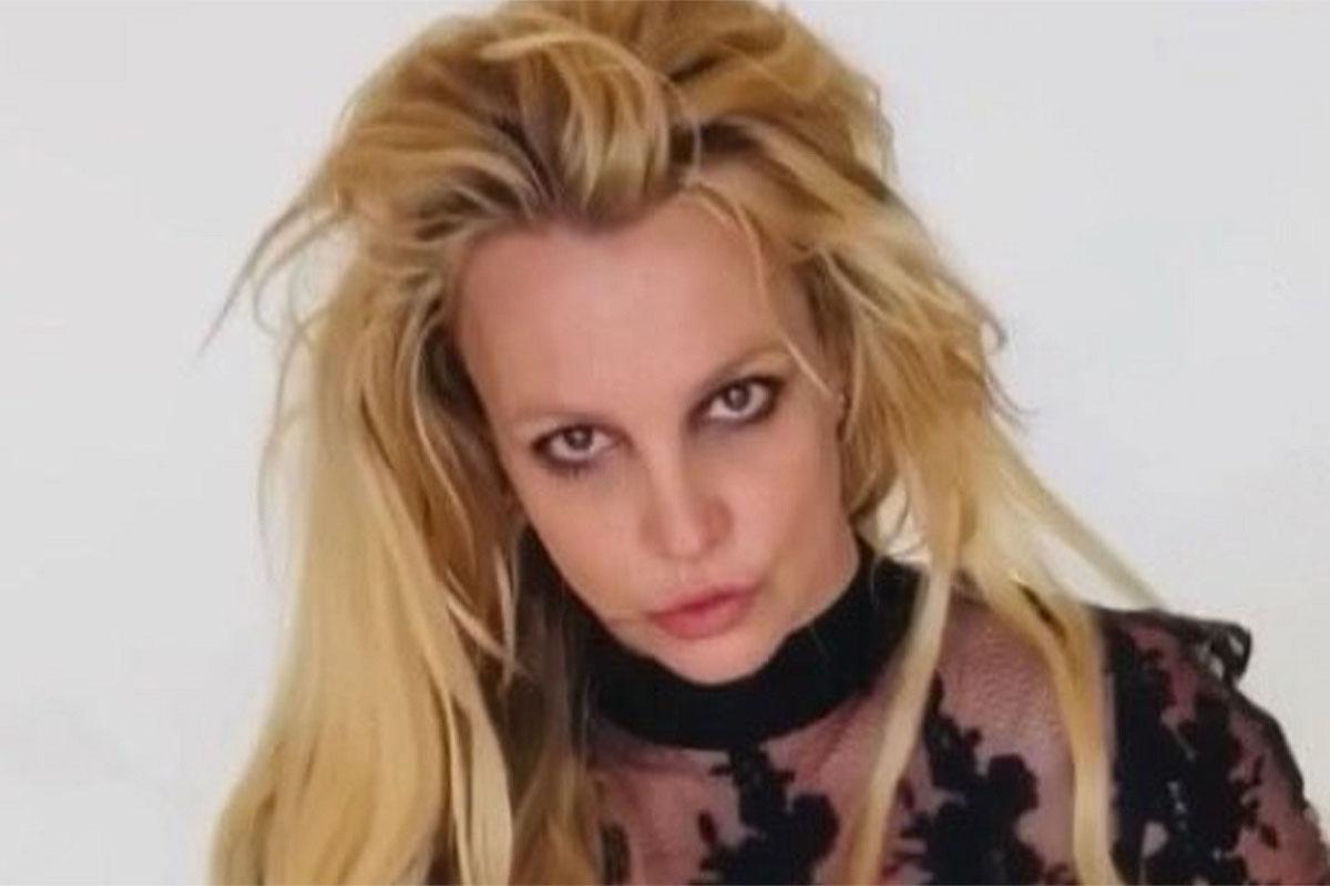 Britney Spears com os cabelos despenteados e blusa transparente
