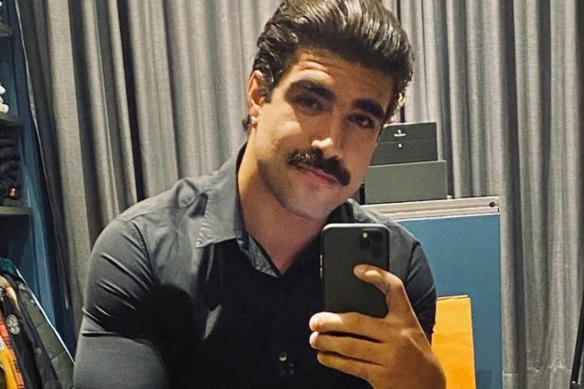 caio castro de bigode tirando uma selfie dentro de seu closet