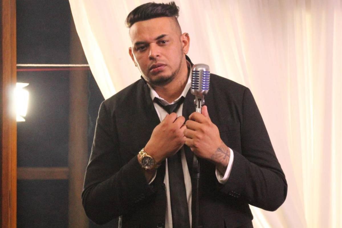 cantor cacau jr. de terno e segurando gravata e o microfone de lapela