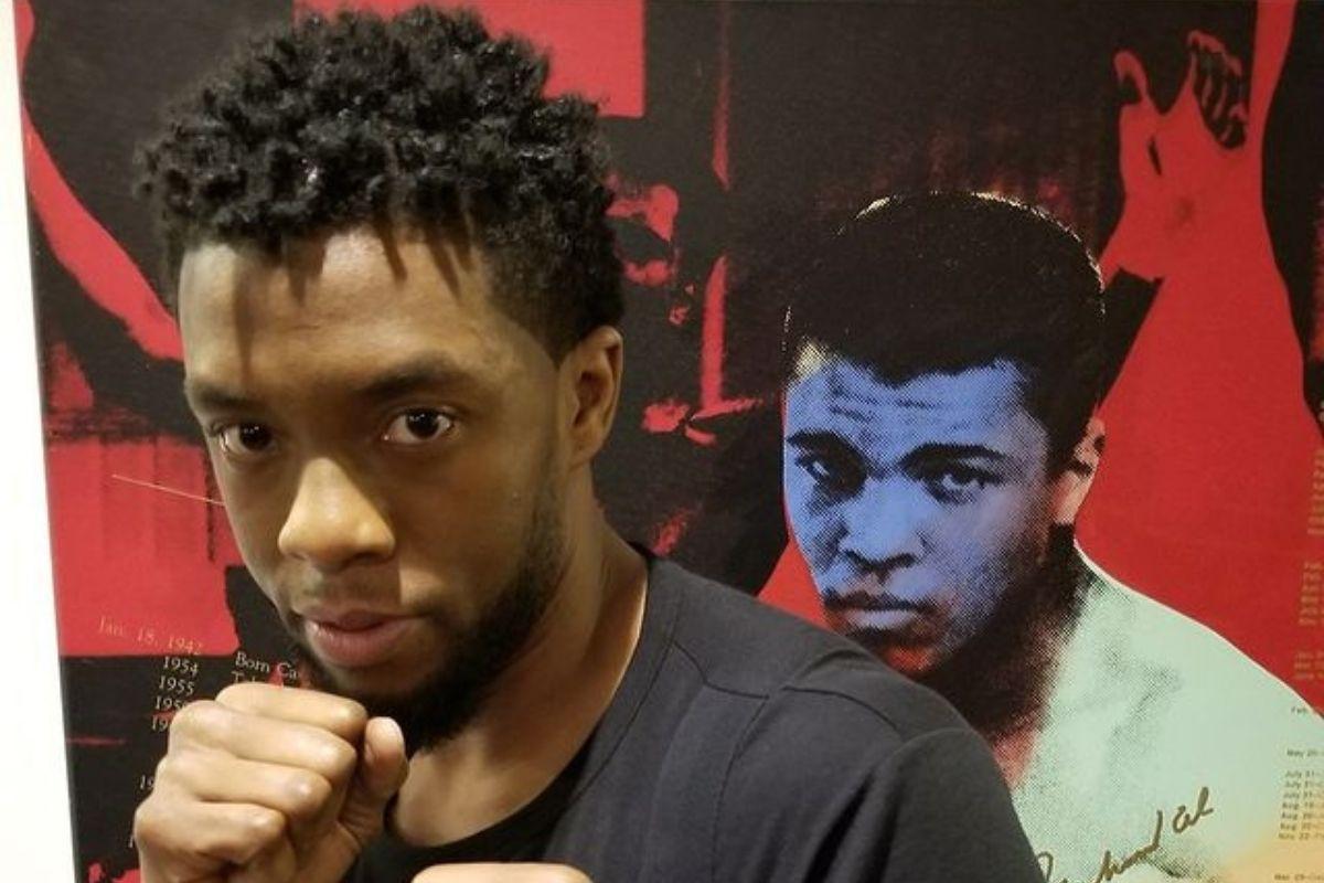 Chadwick Boseman em foto com a imagem do Muhammad Ali atrás