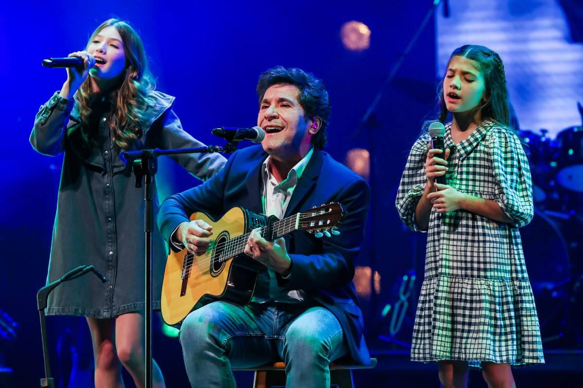 daniel tocando violão enquanto canta ao lado das filhas laura e luiza