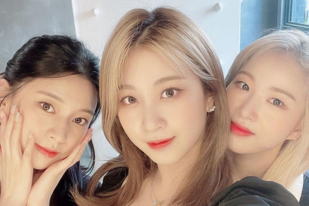 Selfie com Yurim sorrindo com as mãos no rosto, Haeun ao lado, sorrindo e segurando a câmera, e Yuji ao lado, sorrindo