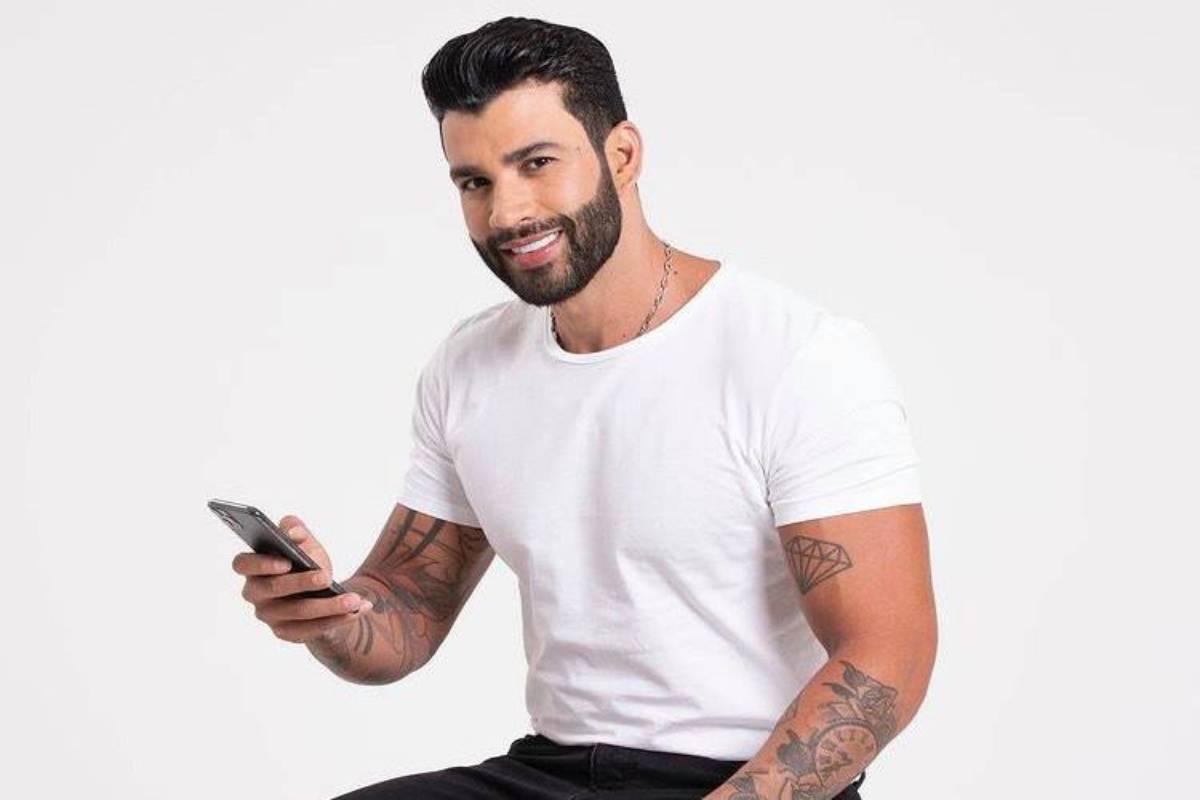 gusttavo lima com camisa branca em foto segurando o celular