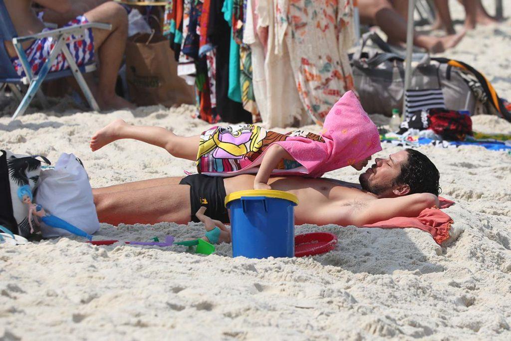 José Loreto ganha beijinho da filha Bella, na praia