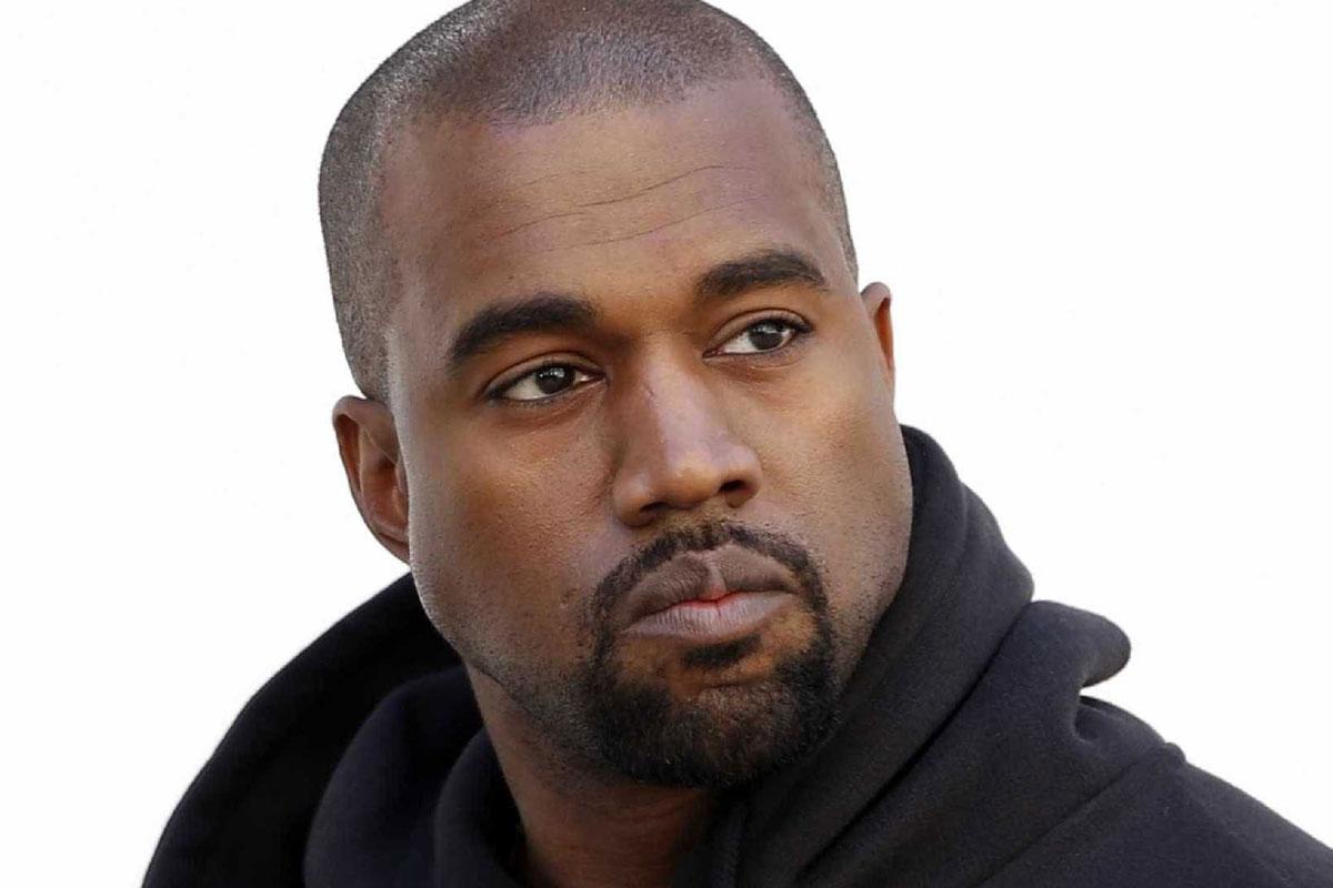 Foto de Kanye West sério, vestindo um casaco de moletom preto e o fundo da imagem branco