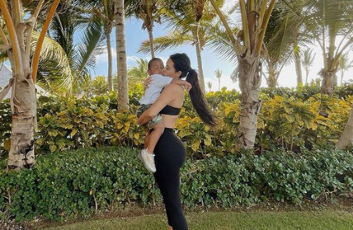 Kim Kardashian beija o filho Saint em um jardim