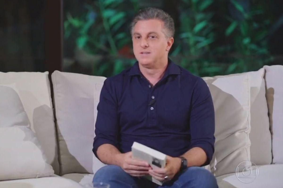 Luciano Huck sentado de camisa preta